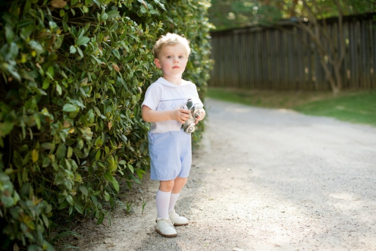 little boy with blonde hair standing with airplane toy