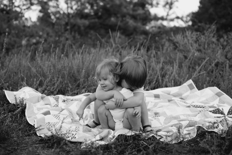 siblings hugging in open field with quilt