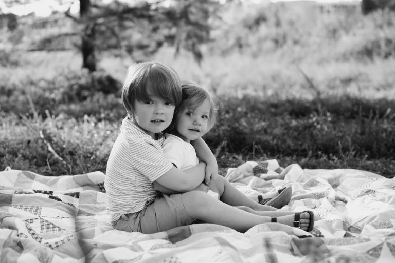 brother and sister portraits in field